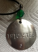 Trickster hand stamped on silver with acrylic faceted bead on black satin cord