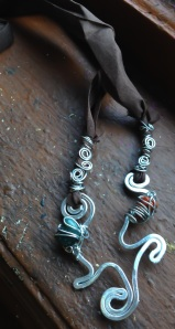 Rich chocolate brown ribbon paired with waves of silver wrapped with goddess spirals, deep green and carnelian