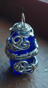A royal blue rectangular piece of glass is wrapped in woven silver wire - a very intricate piece!