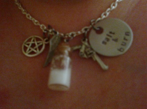 A salt 'n burn necklace with a pentagram, an angel wing, a pistol, and a handstamped Salt n Burn charm! Kelly's ready to face everything from vengeful spirits to demons!